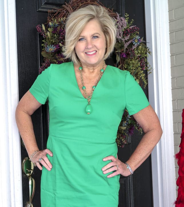Fashion Blogger 50 Is Not Old is wearing a gorgeous bright green sheath dress and a vintage green necklace