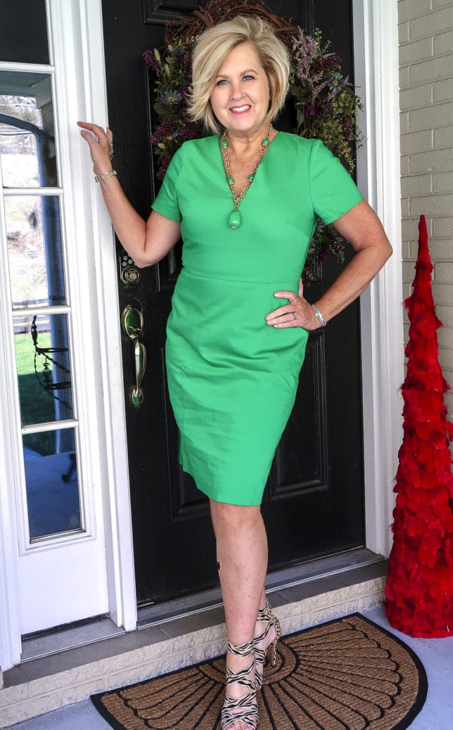 Fashion Blogger 50 Is Not Old is wearing a gorgeous bright green sheath dress, high heel shoes, and a vintage green necklace