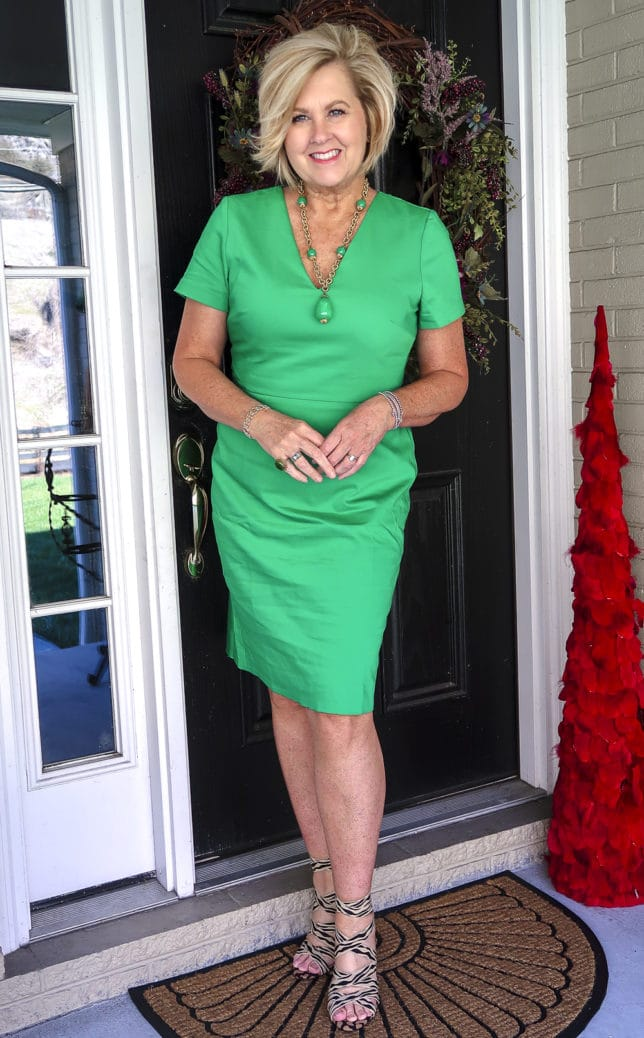 Fashion Blogger 50 Is Not Old is wearing a gorgeous bright green sheath dress, zebra and cheetah print shoes, and a vintage necklace
