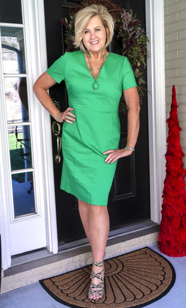 Fashion Blogger 50 Is Not Old is wearing a gorgeous bright green sheath dress, zebra and cheetah print shoes, and a vintage green necklace