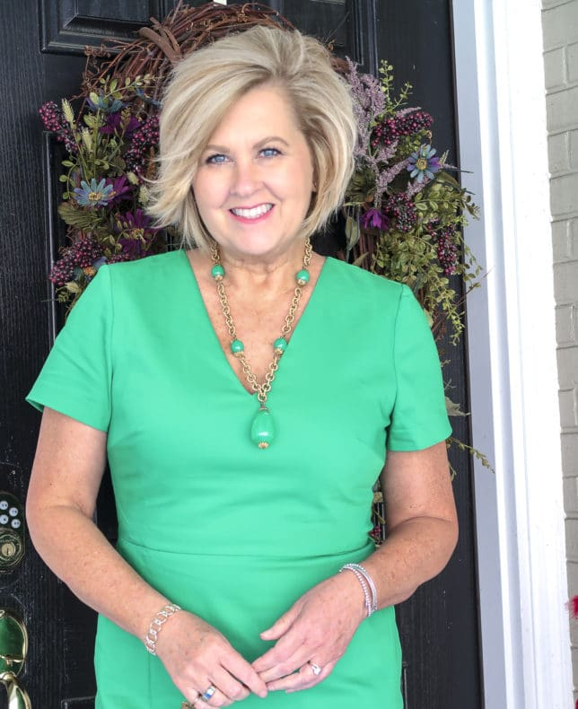 Fashion Blogger 50 Is Not Old is wearing a bright green sheath dress and a vintage green necklace