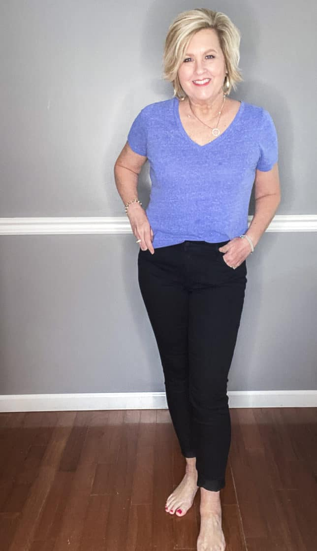 Fashion Blogger 50 Is Not Old wearing a pair of black jeans and a blue v-neck t-shirt