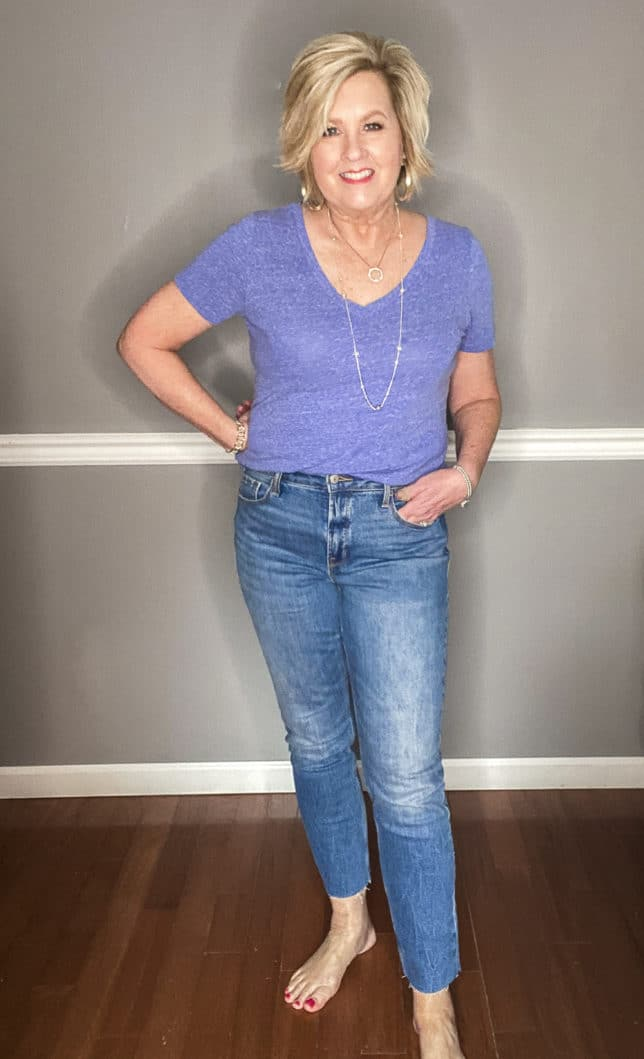 Fashion Blogger 50 Is Not Old wearing a pair of straight raw hem jeans from Old Navy and a blue v-neck t-shirt