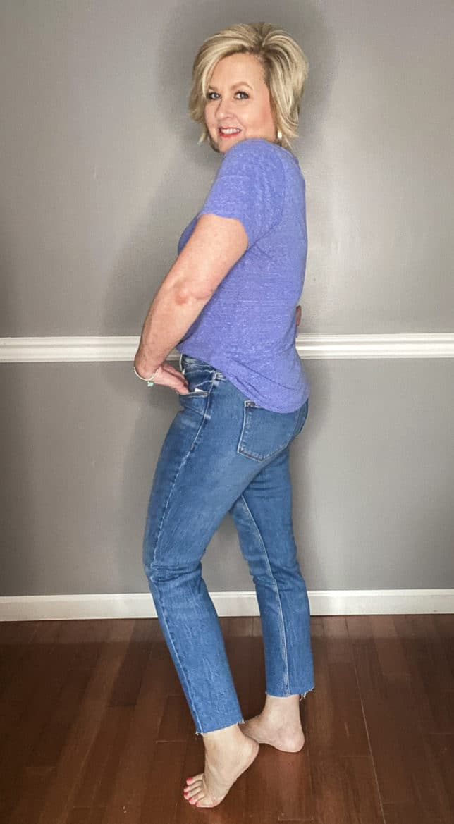 Fashion Blogger 50 Is Not Old showing the fit of a pair of straight raw hem jeans from Old Navy and a blue v-neck t-shirt