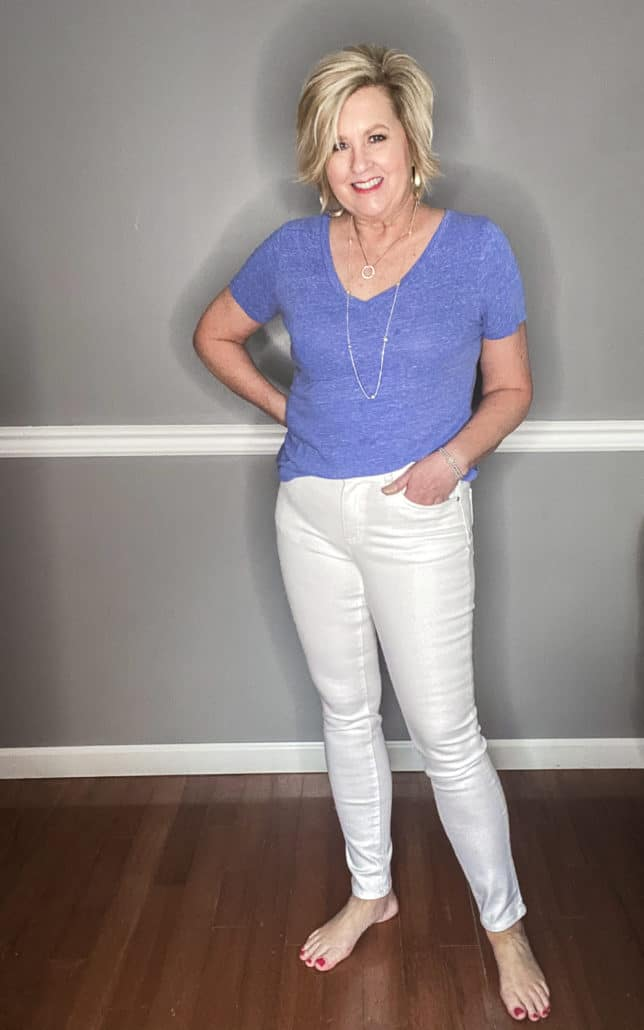 Fashion Blogger 50 Is Not Old wearing a pair of white jeans and a blue v-neck t-shirt