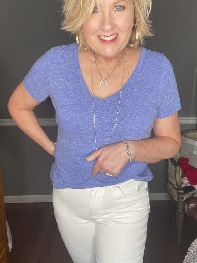 Fashion Blogger 50 Is Not Old showing a pair of white jeans and a blue v-neck t-shirt