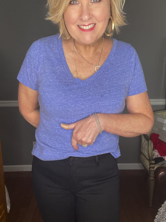 Fashion Blogger 50 Is Not Old wearing a pair of black skinny jeans and a blue t-shirt