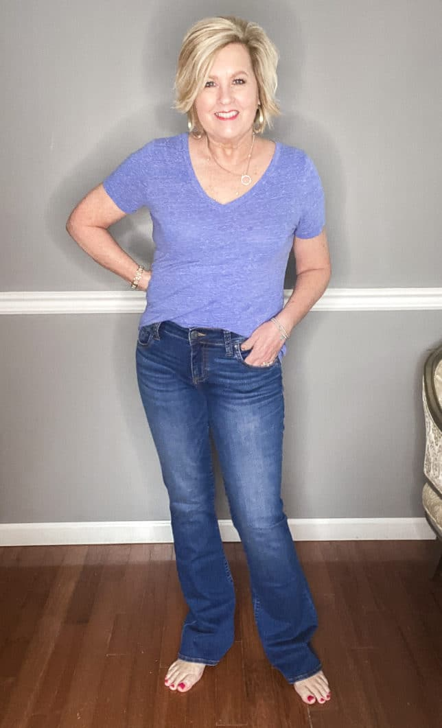 Fashion Blogger 50 Is Not Old showing a pair of blue flare jeans from Kut From The Kloth and a blue v-neck t-shirt