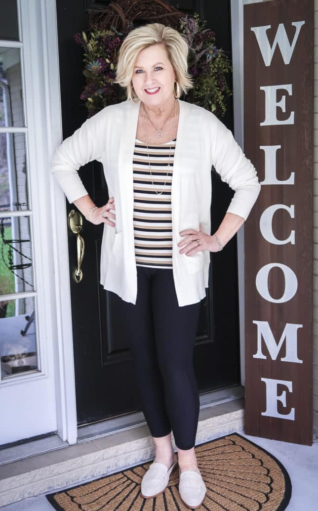 Fashion Blogger 50 Is Not Old wearing a striped tank top, black leggings, a white cardigan, and linen slides