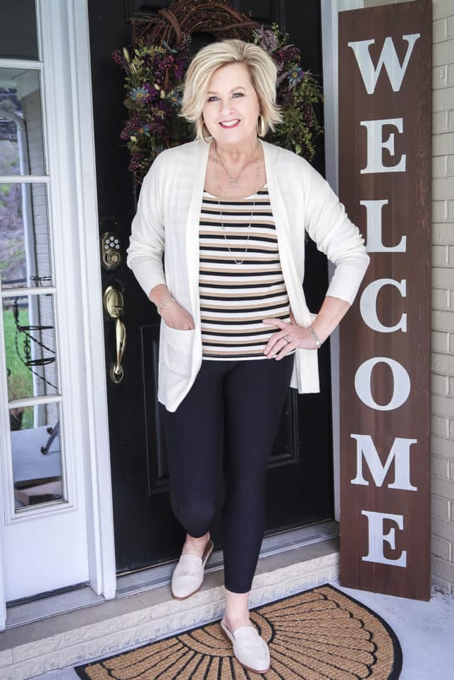 Fashion Blogger 50 Is Not Old wearing a striped tank top, black leggings, a white long cardigan, and linen slides
