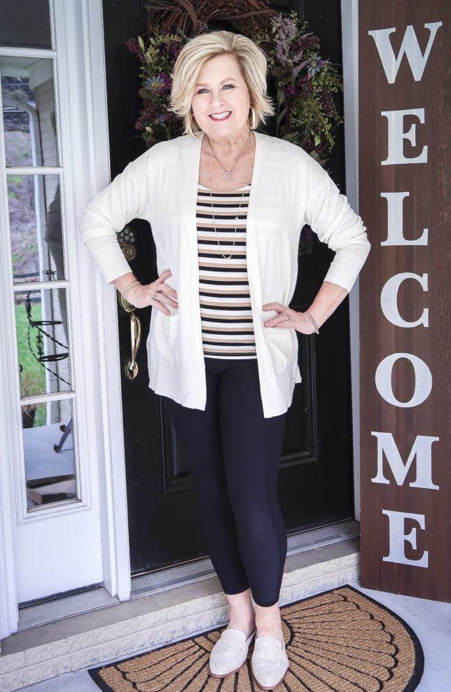 Fashion Blogger 50 Is Not Old wearing a striped tank top, black leggings, a white cardigan, and linen slides from Target