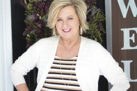 Fashion Blogger 50 Is Not Old wearing a striped tank top and a white long cardigan