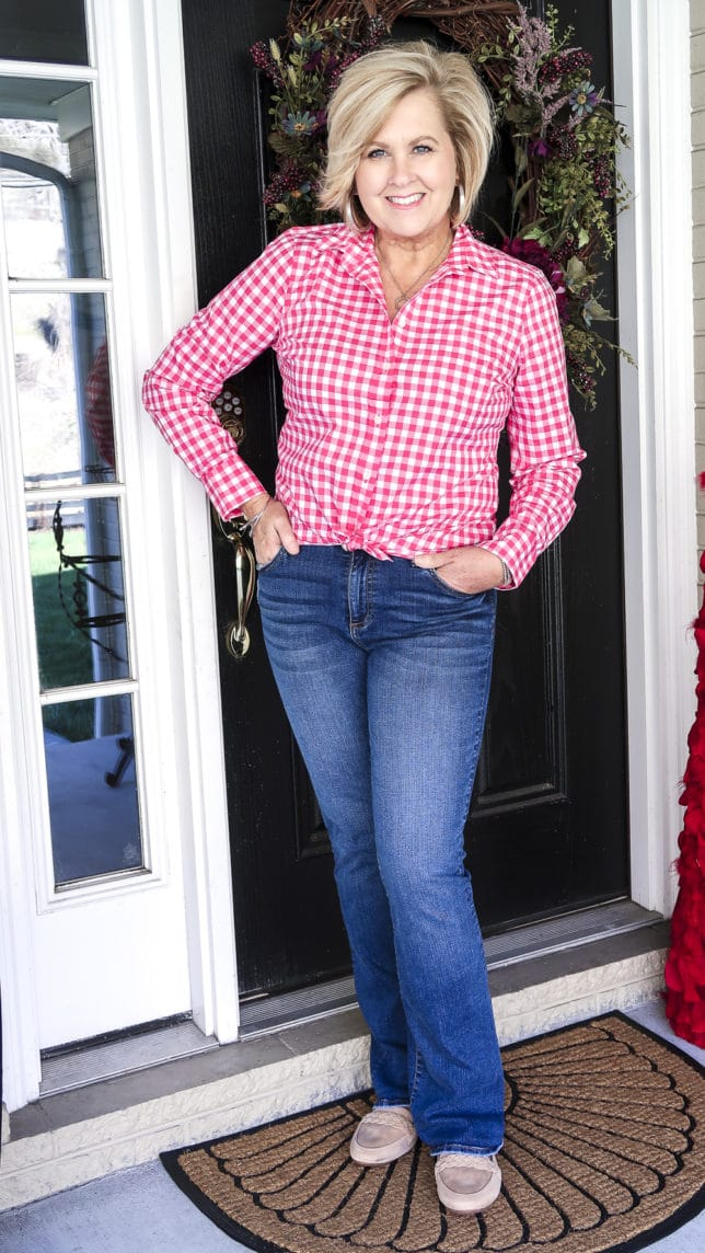 Fashion Blogger 50 Is Not Old is wearing a perfect outfit for spring, a pink gingham shirt, and bootcut jeans