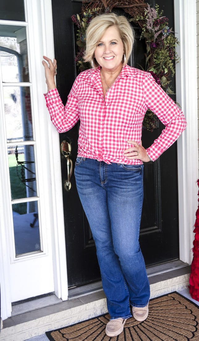 Fashion Blogger 50 Is Not Old is wearing a pink gingham shirt, and bootcut jeans