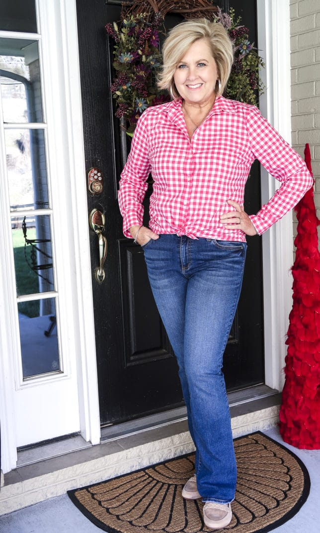 Fashion Blogger 50 Is Not Old is wearing a pink button-up gingham shirt, and bootcut jeans