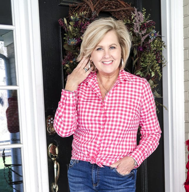 Fashion Blogger 50 Is Not Old is wearing a perfect outfit for spring, a pink gingham shirt, and silver jewelry