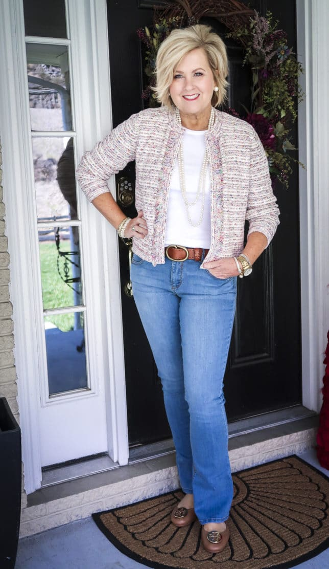 Fashion Blogger 50 Is Not Old is wearing a white t-shirt, bootcut jeans with a brown belt, and a multi-colored blazer