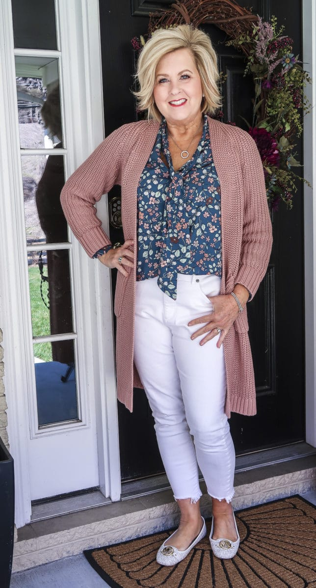 Fashion Blogger 50 Is Not Old is wearing white jeans with a blue floral blouse and a chunky knit cardigan