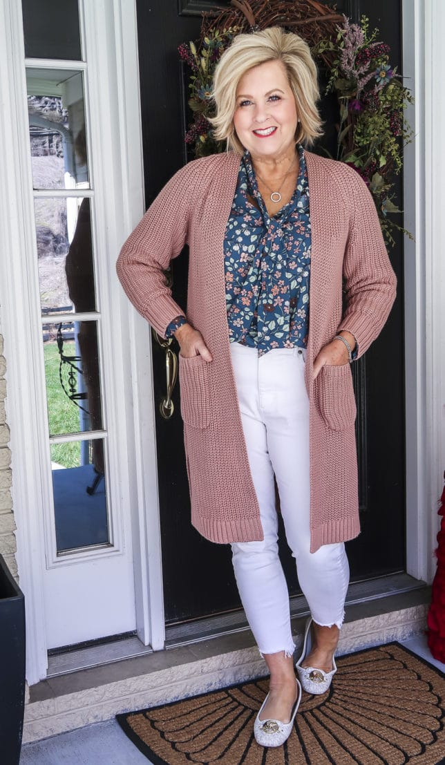 Fashion Blogger 50 Is Not Old is wearing white jeans before Memorial Day with a blue floral blouse, a pink chunky knit cardigan, and white loafers