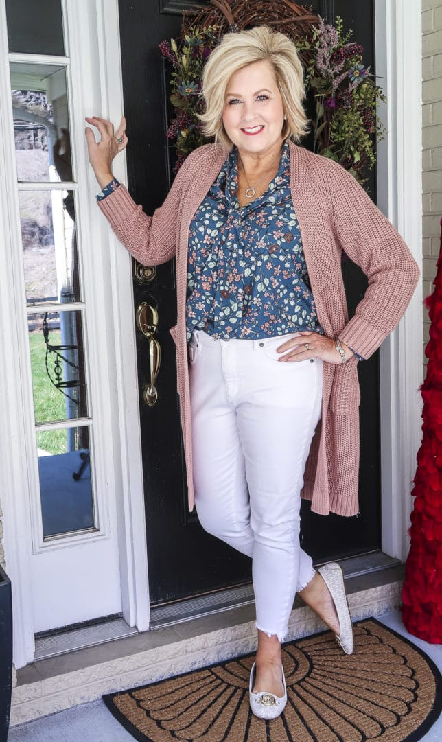Fashion Blogger 50 Is Not Old is wearing white jeans before Memorial Day with a blue floral blouse, a chunky knit cardigan, and white loafers by Michael Kors