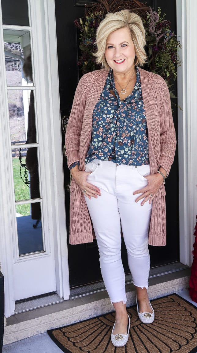 Fashion Blogger 50 Is Not Old is wearing white jeans before Memorial Day with a blue floral blouse and a chunky knit cardigan