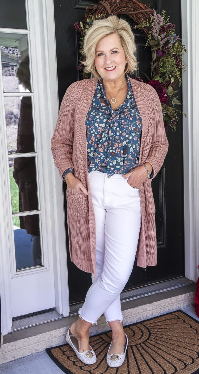 Fashion Blogger 50 Is Not Old is wearing white jeans before Memorial Day with a blue floral blouse, a chunky knit cardigan, and white loafers