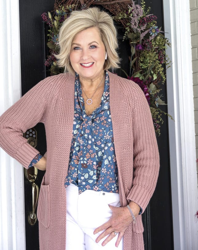 Fashion Blogger 50 Is Not Old is wearing a blue floral blouse and a pink chunky knit cardigan