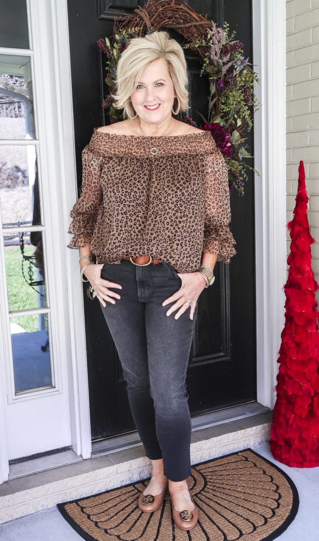 Fashion Blogger 50 Is Not Old wearing a leopard print top and black jeans with a brown belt