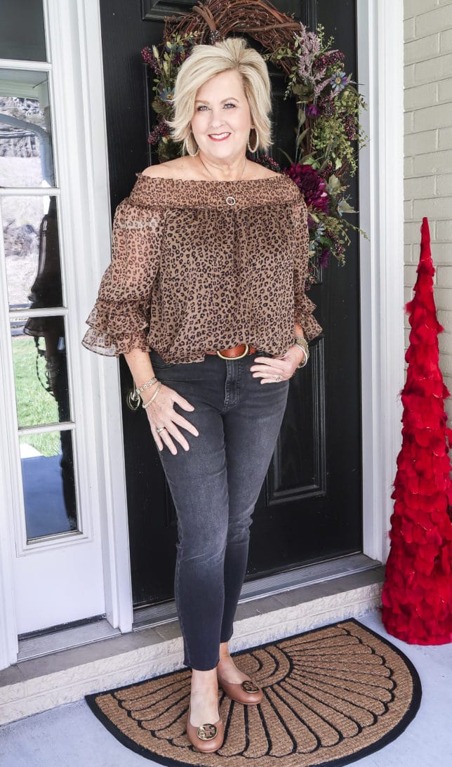Fashion Blogger 50 Is Not Old wearing a leopard print top, black jeans, and a brown belt