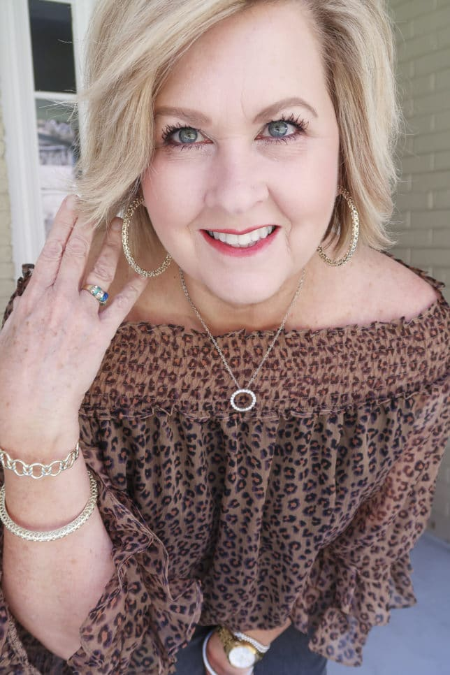 Fashion Blogger 50 Is Not Old wearing a leopard print top and gold jewelry