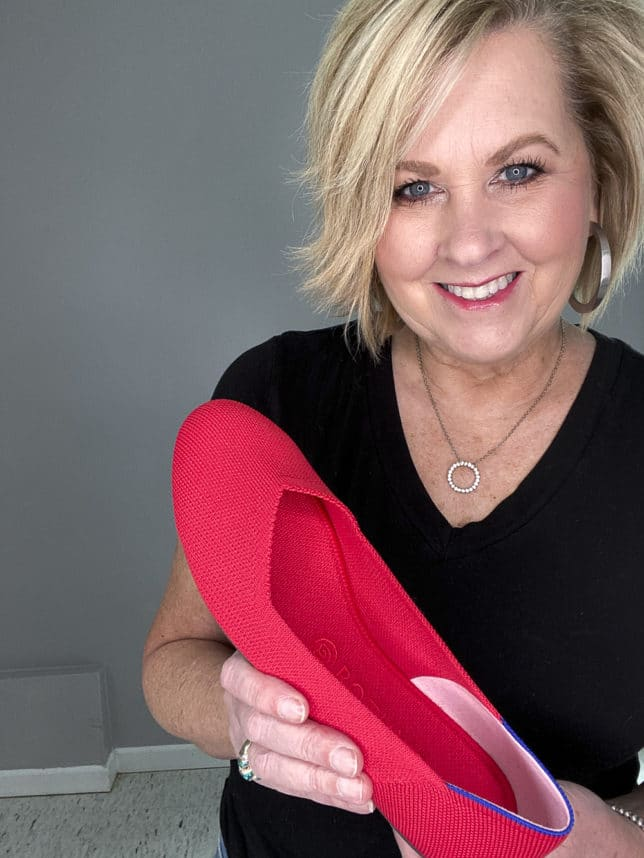FASHION BLOGGER 50 IS NOT OLD HOLDING RUBY RED SHOES FROM ROTHY'S