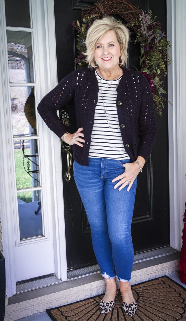 Fashion Blogger 50 Is Not Old is wearing a striped t-shirt with a navy crochet cardigan, chewed hem jeans, and leopard flats