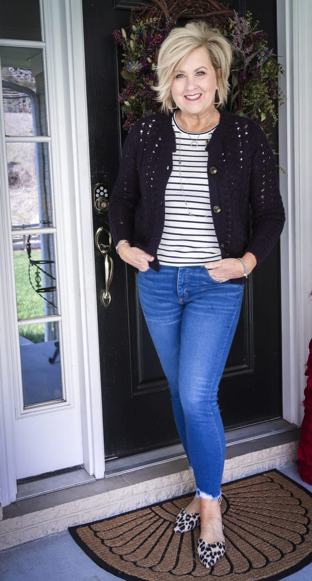 Fashion Blogger 50 Is Not Old is wearing a striped t-shirt with a navy crochet cardigan, chewed hem jeans, and leopard print flats