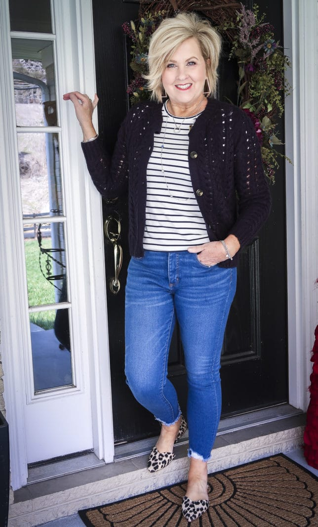 Fashion Blogger 50 Is Not Old is wearing a striped t-shirt with a navy cardigan, chewed hem jeans, and leopard print flats