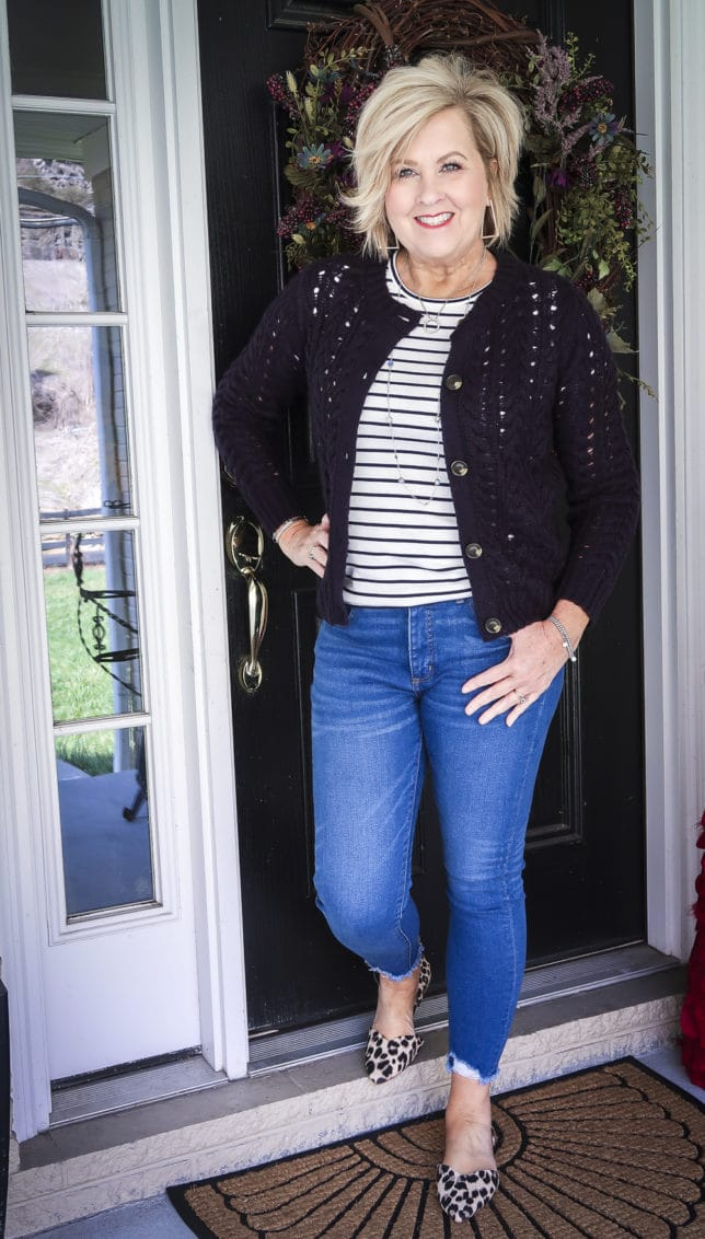 Fashion Blogger 50 Is Not Old is wearing a striped shirt with a navy cardigan, chewed hem jeans, and leopard print flats