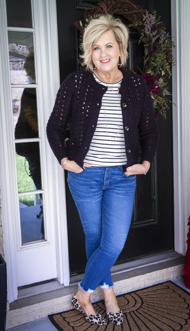 Fashion Blogger 50 Is Not Old is wearing a striped tee with a navy crochet cardigan, chewed hem jeans, and leopard print flats