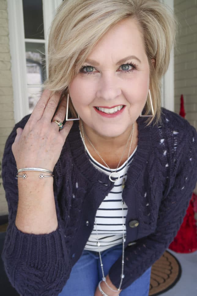 Fashion Blogger 50 Is Not Old is wearing a striped t-shirt with a navy crochet cardigan and silver jewelry