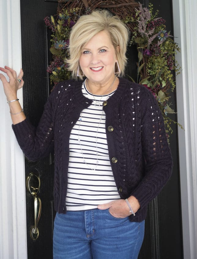 Fashion Blogger 50 Is Not Old is wearing a striped shirt with a navy crochet cardigan