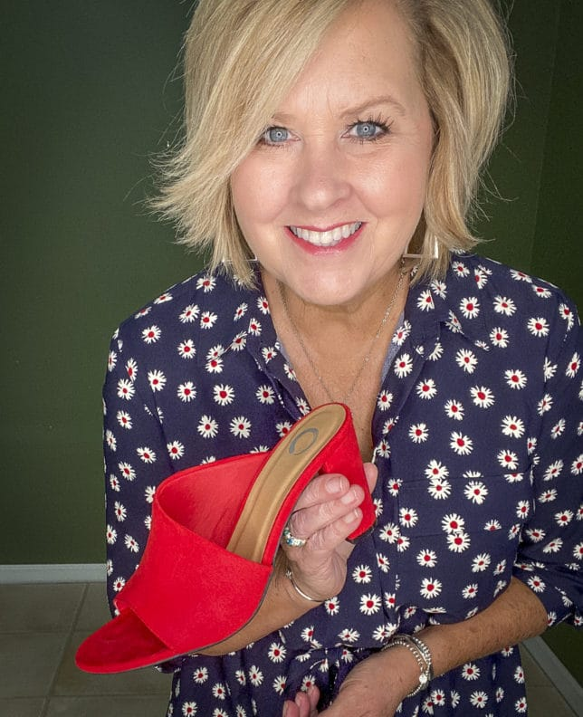 Fashion Blogger 50 Is Not Old wearing a fashionable navy dress with white daisies and bright red shoes from Walmart