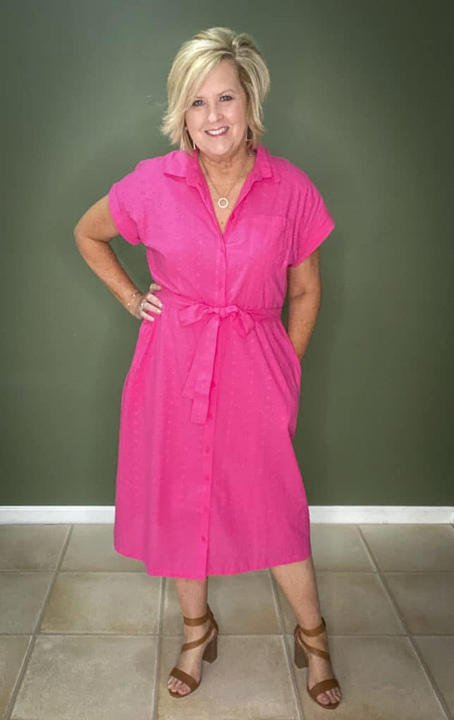 Fashion Blogger 50 Is Not Old wearing a bright pink eyelet dress from Walmart