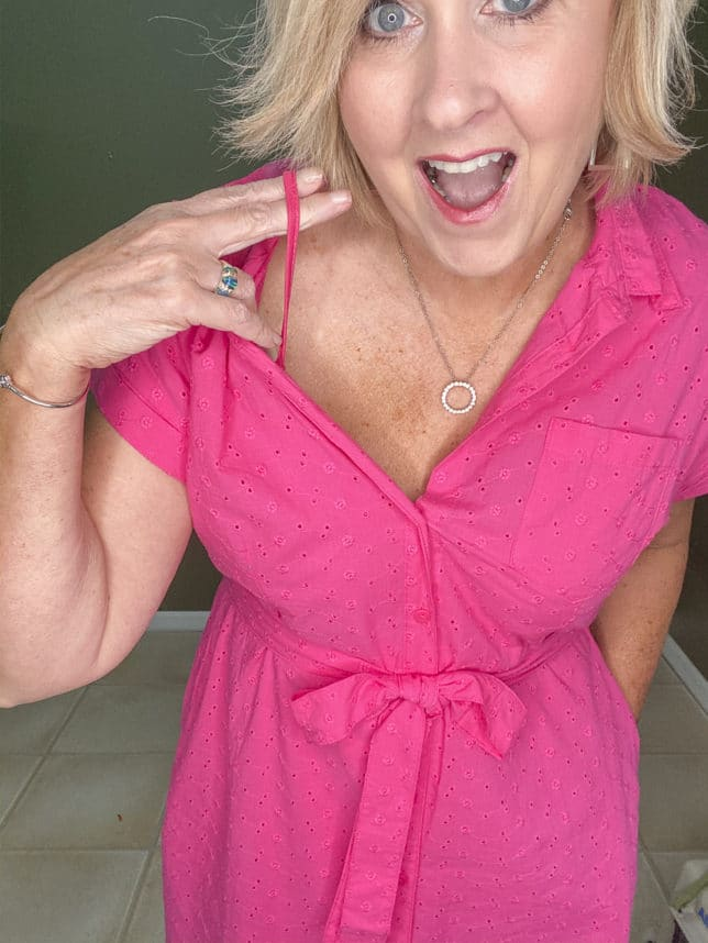 Fashion Blogger 50 Is Not Old wearing a bright pink eyelet dress with a pink slip from Walmart