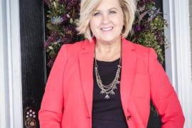 Fashion Blogger 50 Is Not Old is wearing a little black dress and a apple red Pique Knit blazer