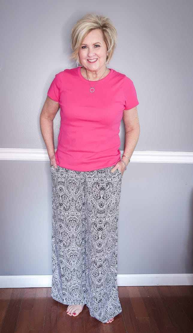 Fashion Blogger 50 Is Not Old is wearing a bright pink t-shirt and black and white paisley wide-leg loungewear pants