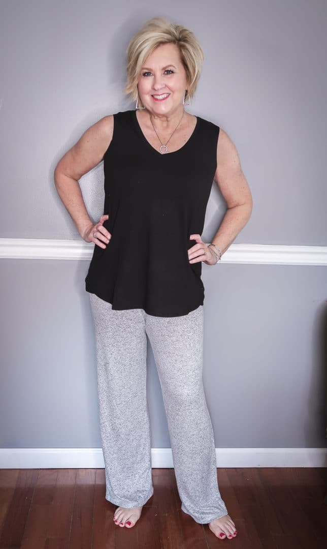 Fashion Blogger 50 Is Not Old is wearing a black tank top and a gray loungewear pant