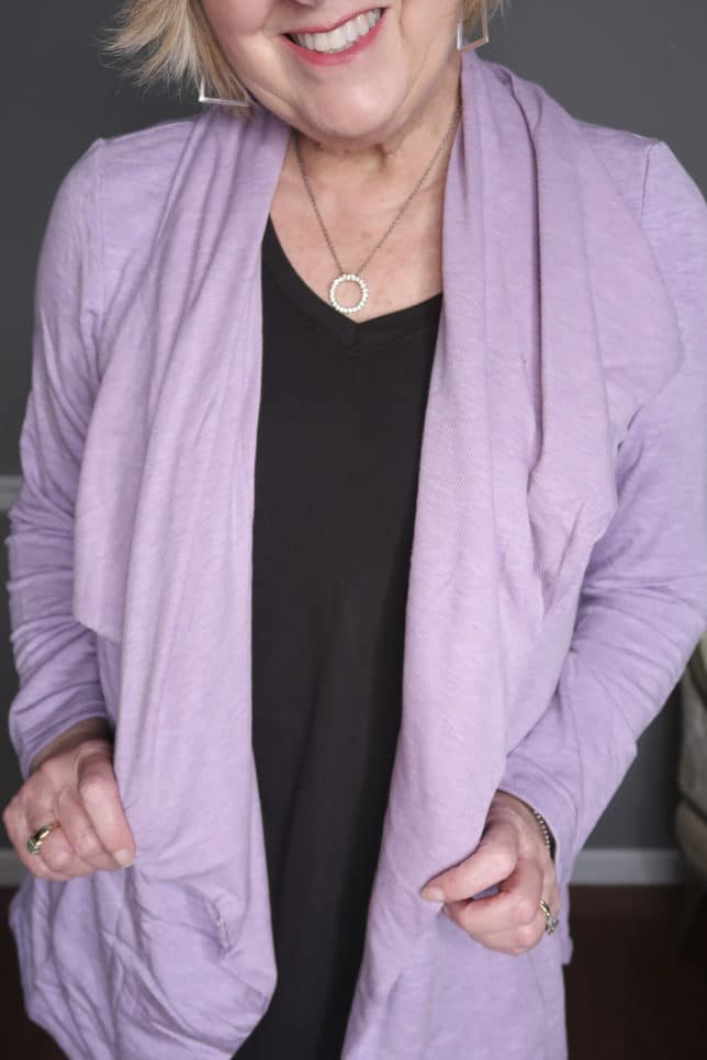 Fashion Blogger 50 Is Not Old is wearing a black tank top with an open lilac cardigan