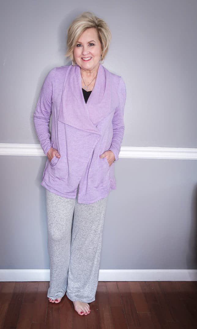 Fashion Blogger 50 Is Not Old is wearing a black tank top with a lilac cardigan and a gray loungewear pant