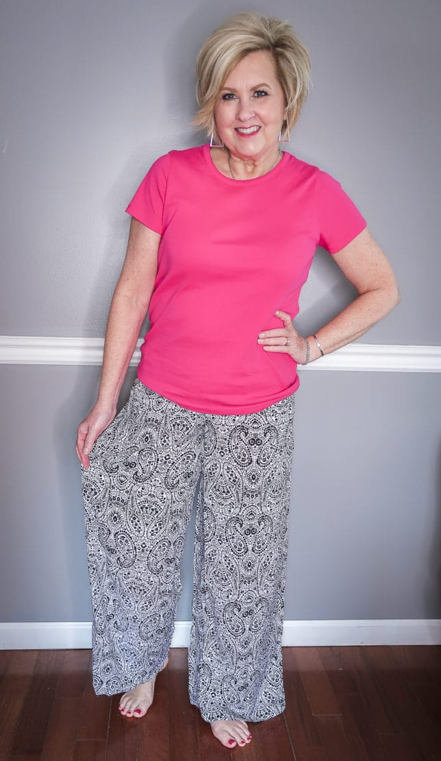 Fashion Blogger 50 Is Not Old is wearing a pink t-shirt and black and white paisley wide-leg loungewear pants