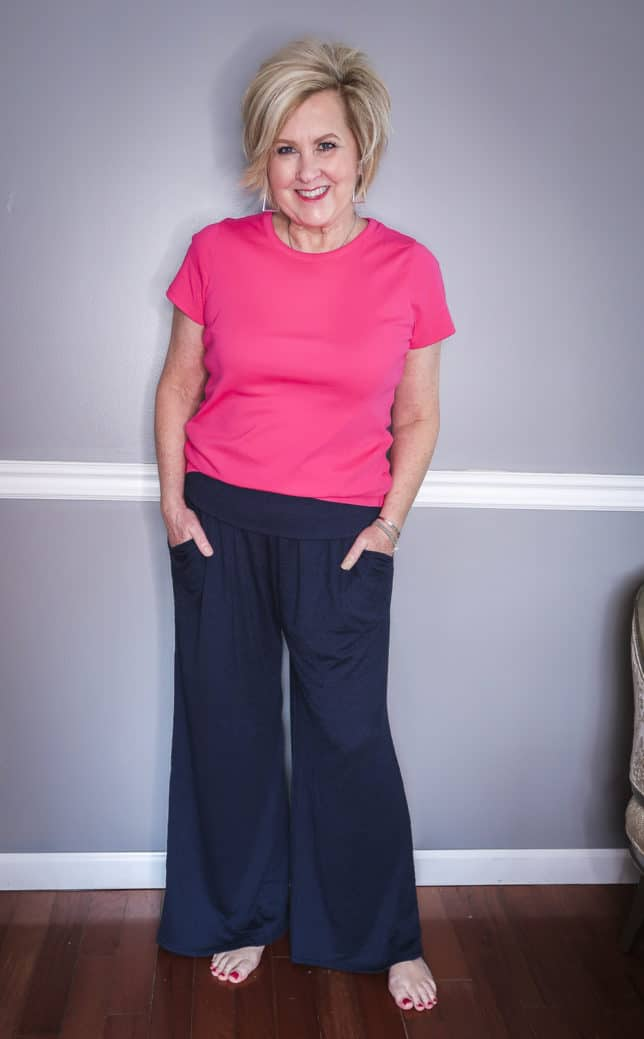 Fashion Blogger 50 Is Not Old is wearing a bright pink t-shirt and navy crinkle wide-leg loungewear pants