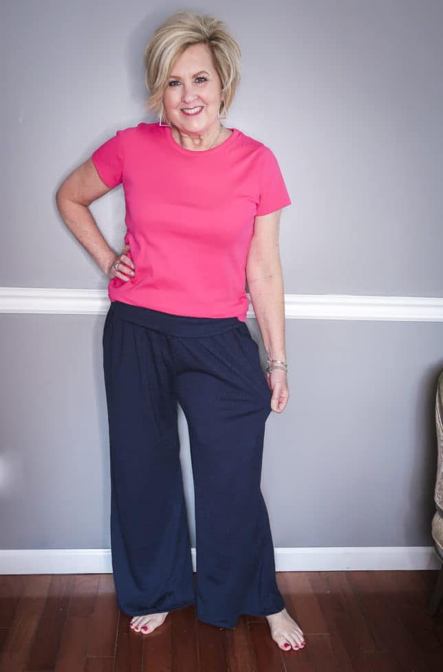 Fashion Blogger 50 Is Not Old is wearing a pink t-shirt and navy crinkle wide-leg loungewear pants