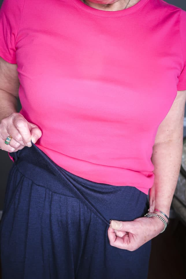 Fashion Blogger 50 Is Not Old is wearing a bright pink tee and navy crinkle wide-leg loungewear pants